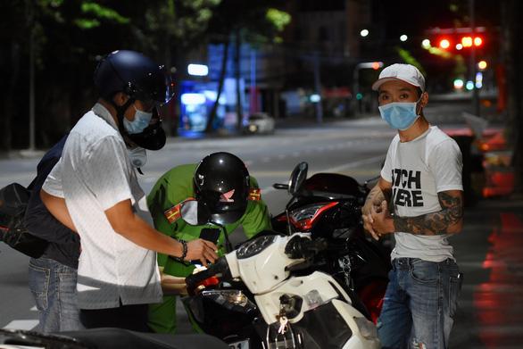 Lực lượng chức năng Đồng Nai xử phạt một thanh niên ra đường không có lý do chính đáng sau 18h - Ảnh: A LỘC