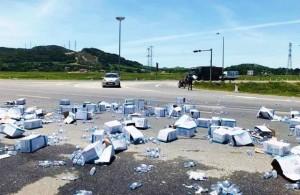 Xe container bị lật, chiến sĩ CSGT giúp thu gom hàng trăm thùng nước đổ giữa đường