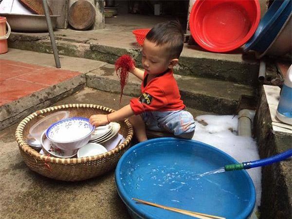 Thấy bố mẹ ăn xong không dọn, bé trai vừa rửa bát vừa nói câu khiến cả nhà